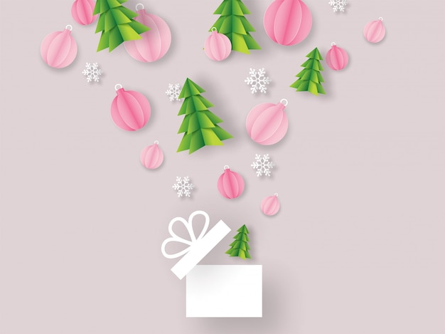 Origami paper cut xmas tree with baubles and snowflakes flying from open surprise gift box on pink background for merry christmas celebration greeting card