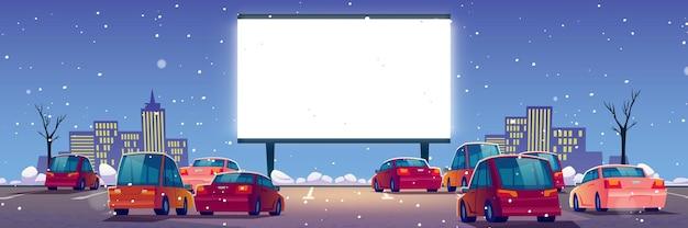 Летний кинотеатр, автомобильный кинотеатр с машинами на открытой парковке зимой.