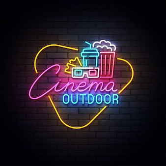 Outdoor cinema neon sign, drive-in movie theater with cars on open air parking