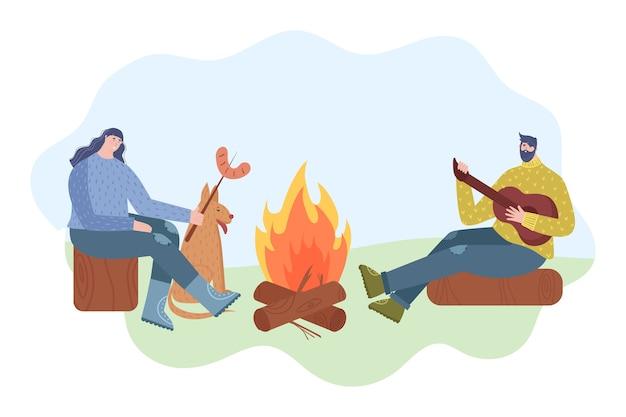 Отдых на свежем воздухе. молодая пара хорошо проводит время. женщина жарит на костре сосиски. мужчина играет на гитаре.