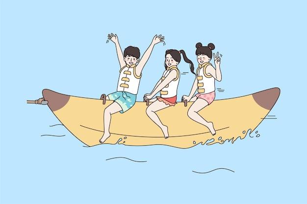기뻐하는 아이들은 바다에서 바나나 보트를 타고 즐겁게 놀고 있습니다.