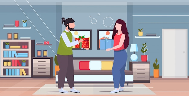 Overweight couple giving surprise boxes presents to each other holiday celebration concept over size man woman in love modern bedroom interior horizontal full length