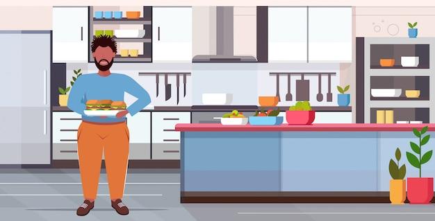 Избыточный вес мужчина держит поднос с гамбургерами нездоровый образ жизни концепция парень есть фаст-фуд современный дом кухня интерьер полная длина плоский горизонтальный