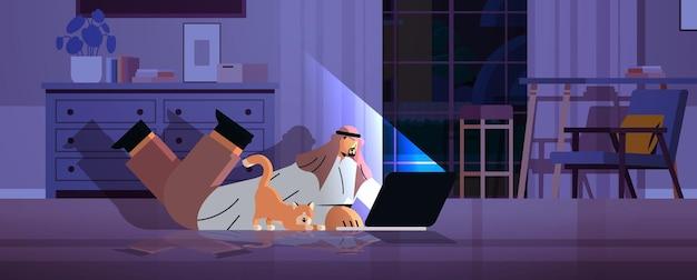 Overworked arab businessman freelancer looking at laptop screen arabic man with dog lying on floor in dark night home room horizontal full length vector illustration