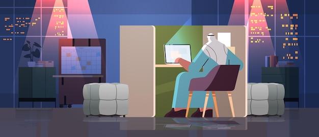 Перегруженный арабский бизнесмен-фрилансер, работающий на ноутбуке арабский человек, сидящий на рабочем месте в темной ночной офисной комнате