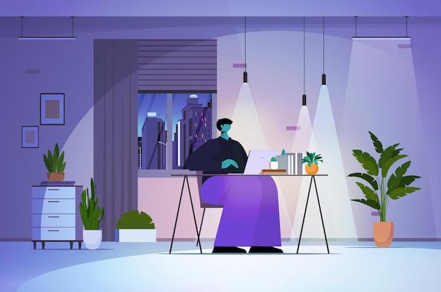 Перегруженный работой бизнесмен, использующий ноутбук в концепции сети социальных сетей темной ночи или гостиной