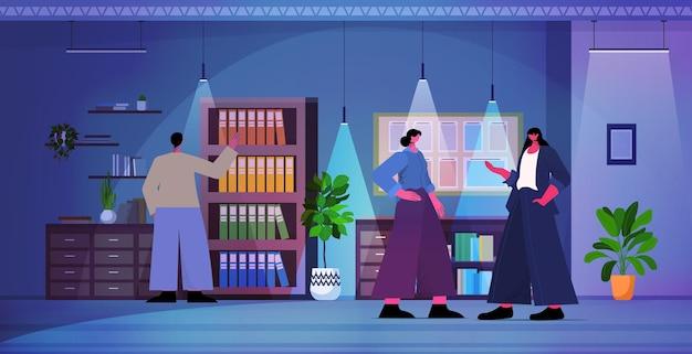 Перегруженные бизнесмены обсуждают во время встречи деловых людей, работающих в современном темном ночном офисе