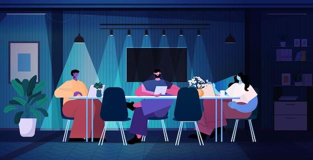 Перегруженные бизнесмены обсуждают во время встречи в современном темном ночном офисе по горизонтали в полный рост