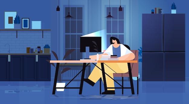 暗い夜のホームオフィスの水平フルレングスでコンピューター画面を見ている職場のビジネスウーマンフリーランサーに座っている過労の実業家