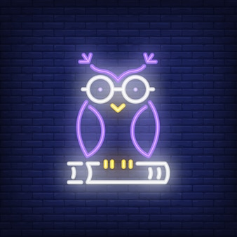 Owl on book neon sign. clever owl in glasses sitting on book. night bright advertisement.