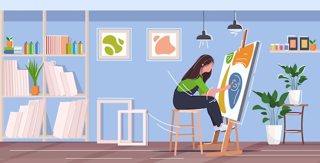 Painter using paintbrush and palette woman artist sitting in front of easel art concept modern workshop studio interior horizontal