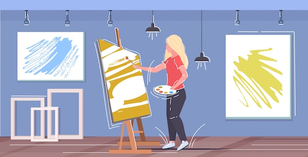 Painter using paintbrush and palette woman artist standing in front of easel art concept modern workshop studio interior horizontal