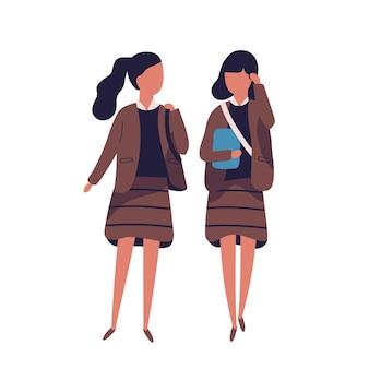 制服を着た女の子のペア。女子学生、生徒、クラスメート、学友が一緒に歩いたり、話したり、おしゃべりしたりします。モダンなフラットスタイルの色付きベクトルイラスト。