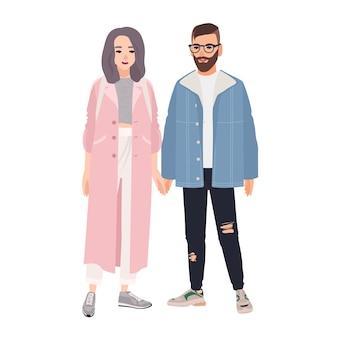 流行に敏感な男性と女性のペアは、一緒に立って手をつないでファッショナブルな服を着ています。スタイリッシュなロマンチックなカップル