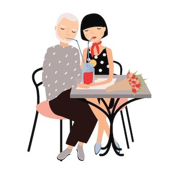 Пара мужчина и женщина сидят за столом и вместе пьют коктейль с трубочкой