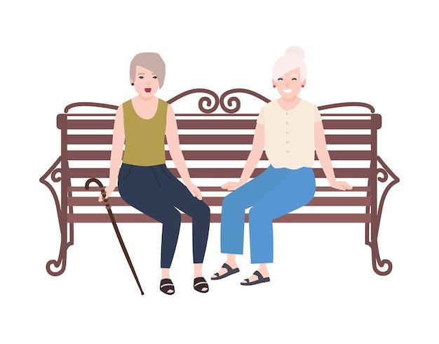 ベンチに座って話している笑顔の年配の女性のペア。 2人の老婦人または友人の幸せな出会い。白い背景で隔離のかわいい平らな女性の漫画のキャラクター。カラフルなベクトルイラスト。