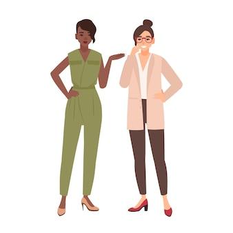 Пара улыбающихся женщин, одетых в деловую одежду, разговаривает друг с другом и смеется