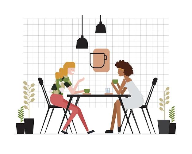 テーブルに座って、お茶を飲み、話しているガールフレンドの若い女性のペア