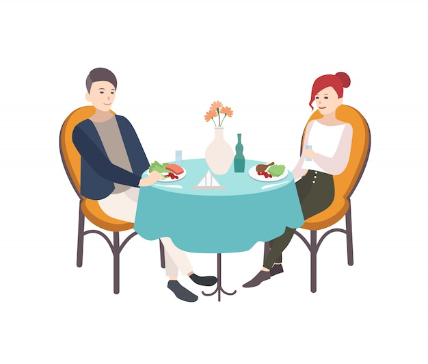 Pair of young man and woman dressed in stylish clothes sitting at table