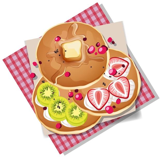 白い背景で隔離のキウイとイチゴのトッピングとパンケーキ