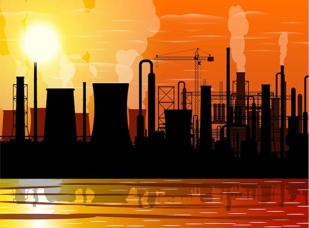 パノラマの産業シルエットの風景。喫煙工場は貯水池を配管します。