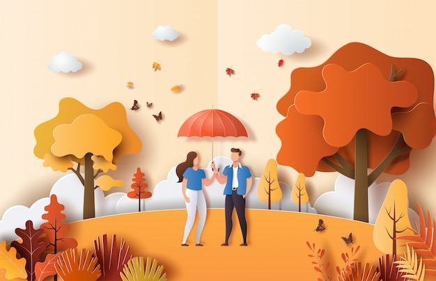 Paper art style of autumn landscape with cute couple in love holding umbrella in a park.