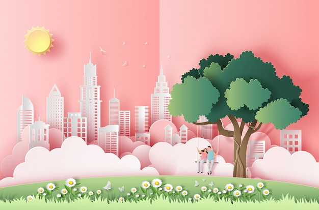 Paper art style of cute couple sitting on a swing under a tree in a big city.