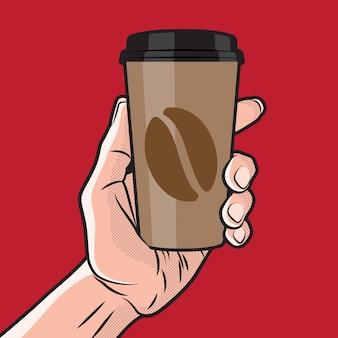 手に紙のコーヒーカップ