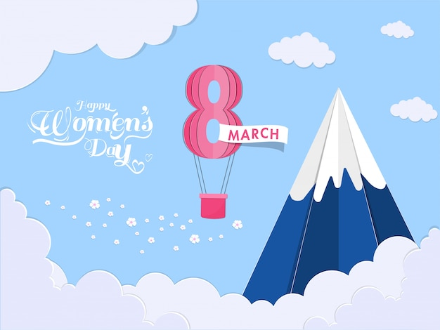 Paper cut cloudy background with snow mountain and 8 march shape hot air balloon for happy women's day celebration concept.