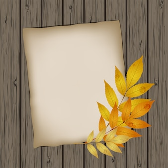 Paper sheet with autumn leaves on wooden table texture.