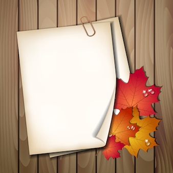 Paper sheet with autumn leaves on wooden table