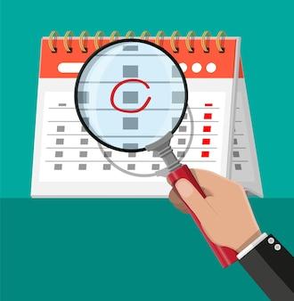 Бумажный спиральный настенный календарь и увеличительное стекло.