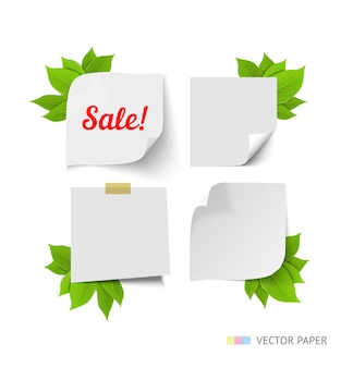 Paper with curl corners set with green leaves isolated on white background