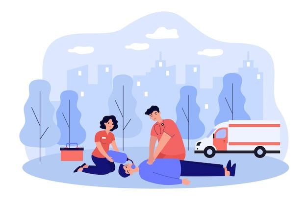 意識不明の人を蘇生させる救急医療。外に横たわるのに心肺蘇生法を適用する医師と助手