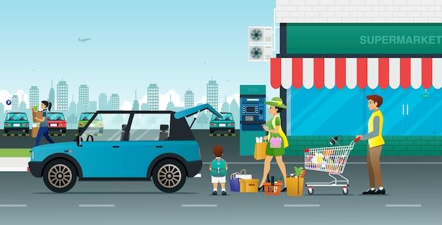 부모와 자녀가 슈퍼마켓에서 자동차로 물건을 운반하고 있습니다.