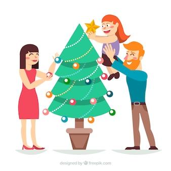 I genitori aiutano la figlia a decorare un albero di natale