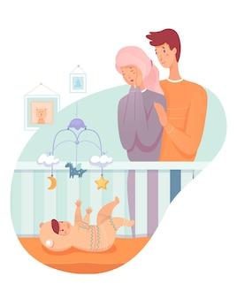 아기가 있는 부모. 젊은 엄마와 아빠는 유아용 침대에서 아기를 바라보고 있습니다. 재미있는 양복을 입은 아이가 유아용 침대 모바일로 재생됩니다.