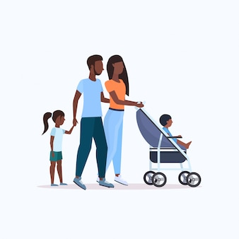 Parents with daughter and toddler son in stroller walking outdoor   family parenthood concept full length