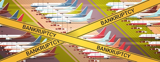 Parked airplanes at taxiway airport terminal with yellow bankruptcy tape coronavirus pandemic