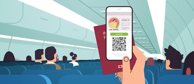 Passenger hand holding digital vaccinate certificate and global immunity passport in airplane coronavirus immunity concept horizontal vector illustration