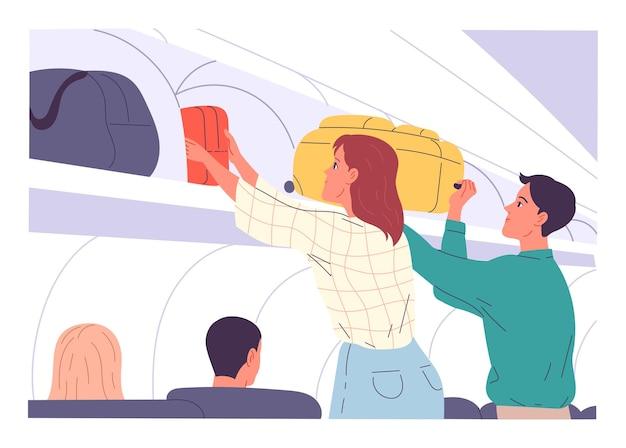 機内持ち込み手荷物を航空機のオーバーヘッドロッカーに入れる乗客。
