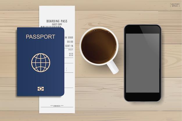 木の背景にコーヒーカップとスマートフォンのパスポートと搭乗券のチケット