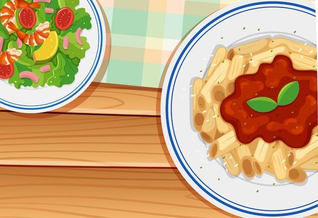 Паста и салат на деревянной доске