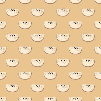 パステルピンクのリンゴのスライスシルエットのシームレスなパターン。ベージュの背景。