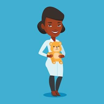 Врач педиатр держит плюшевого мишку.