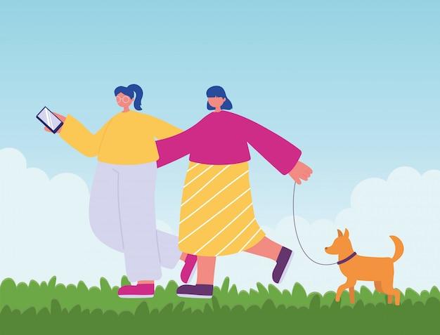 人の活動、犬とスマートフォンで歩く若い女性