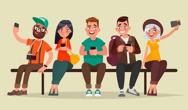 Люди и гаджеты. группа студентов, сидя на скамейке, наслаждаясь мобильными устройствами.