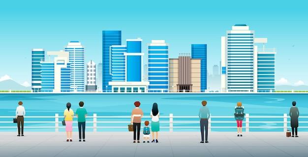 사람들과 관광객들이 바다 옆의 도시 경관을 보고 있다