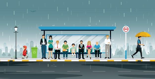 사람들은 비가 오면 버스 정류장에서 기다리고 있습니다.