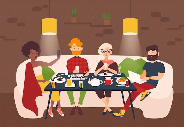 레스토랑 테이블에 앉아 노트북 화면을 응시하는 세련된 옷을 입은 사람들